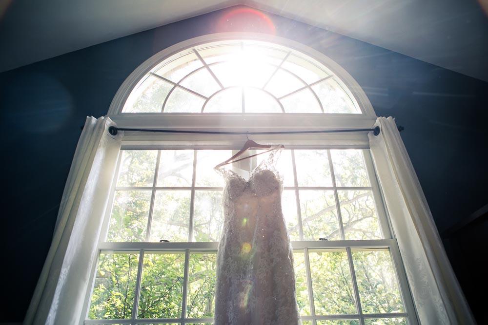 Wedding dress in window with sun flare