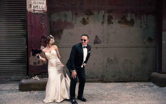 Bride and groom in back alley of Ravenswood Event Center