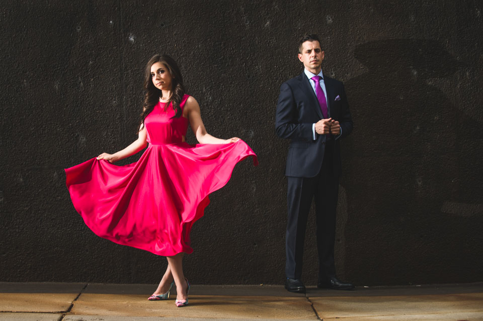 Red dress engagement posed against dark wall