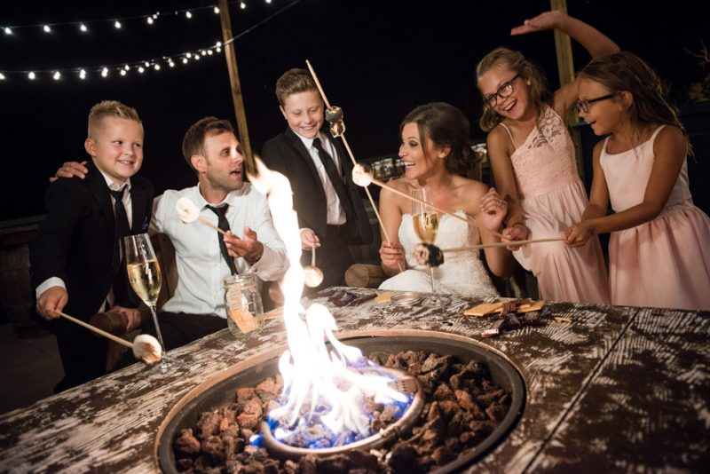 Bride and Groom roasting marshmallows.