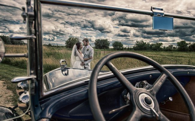 Bride and groom with vintage car on a farm