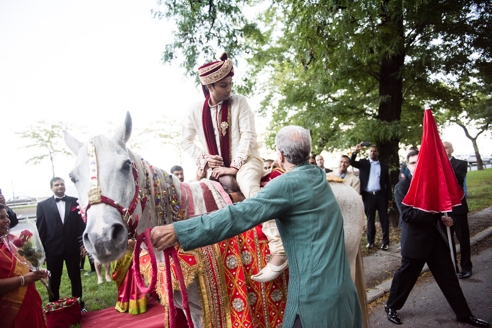 Groom mounting horse for Indian baraat
