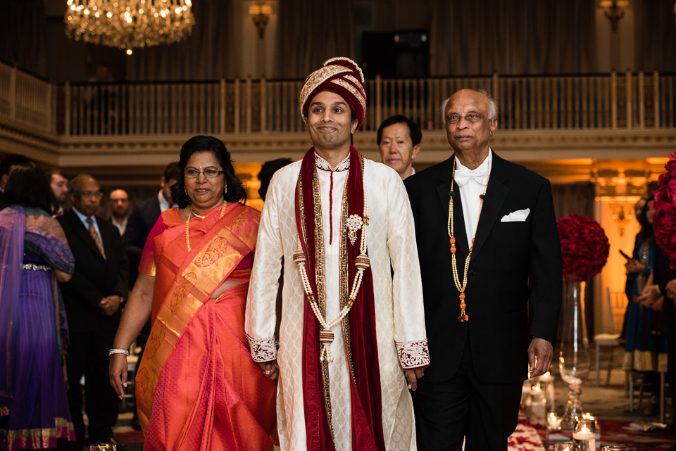 Groom walking down aisle at Indian wedding