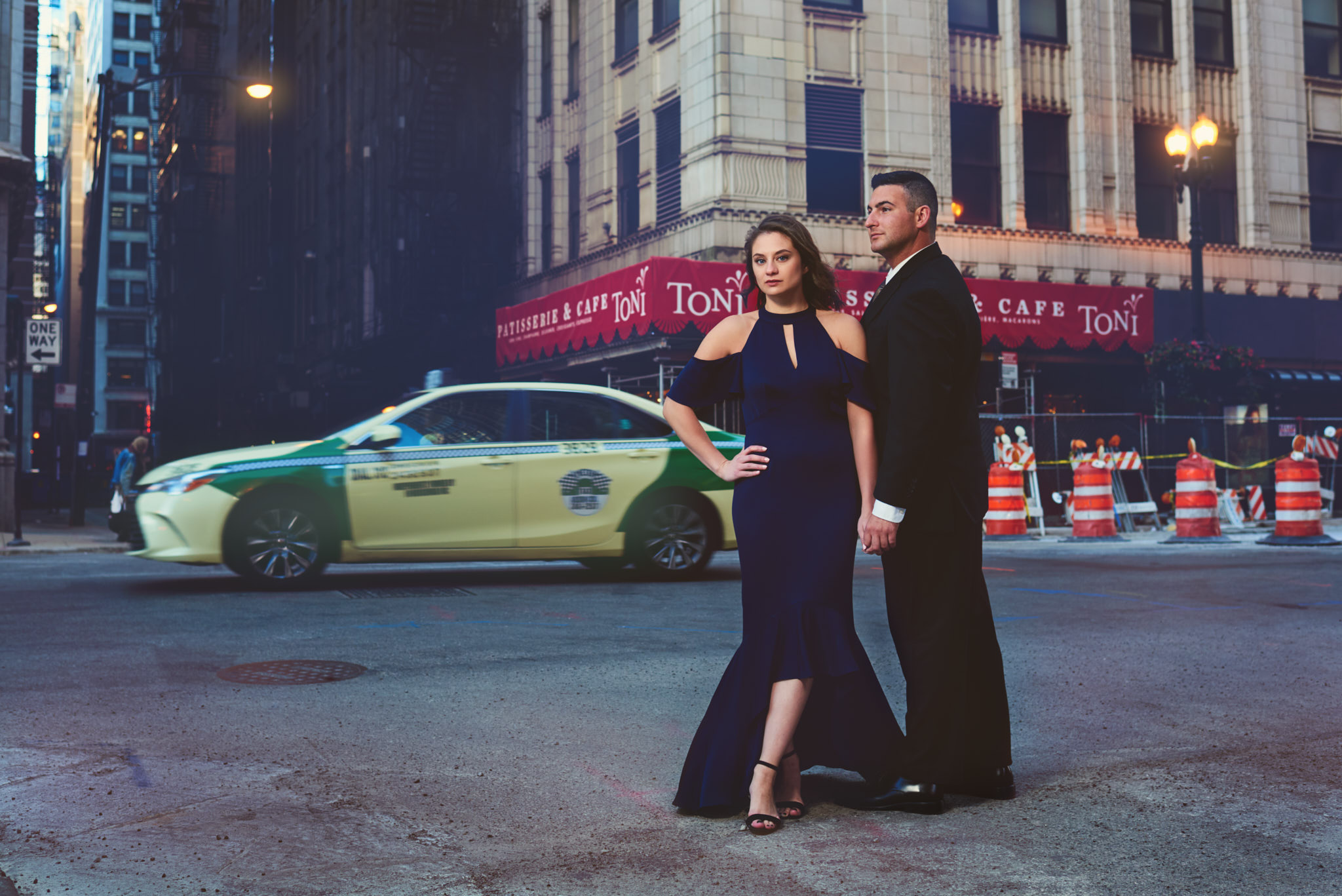 Formal engagement portrait with taxi passing in background
