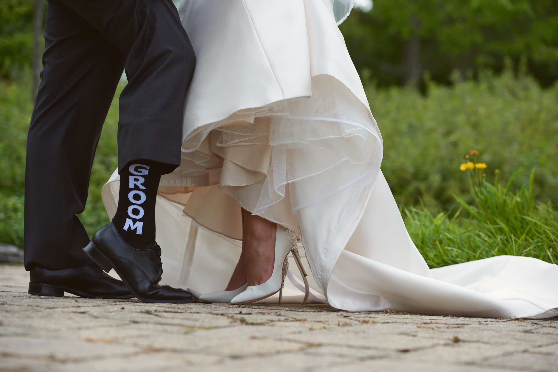 Bride showing shoe and groom showing socks