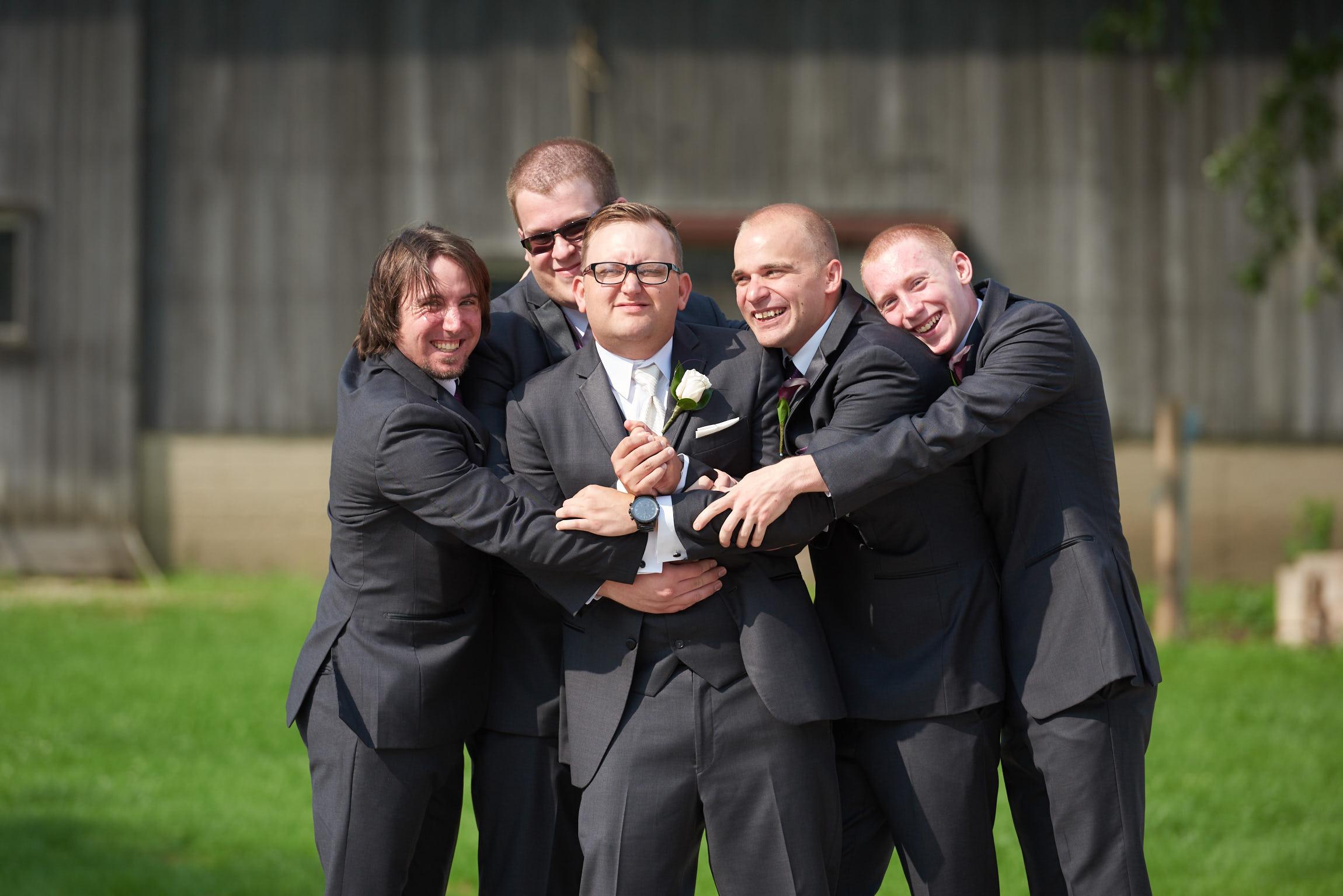 Groomsmen all hugging the groom