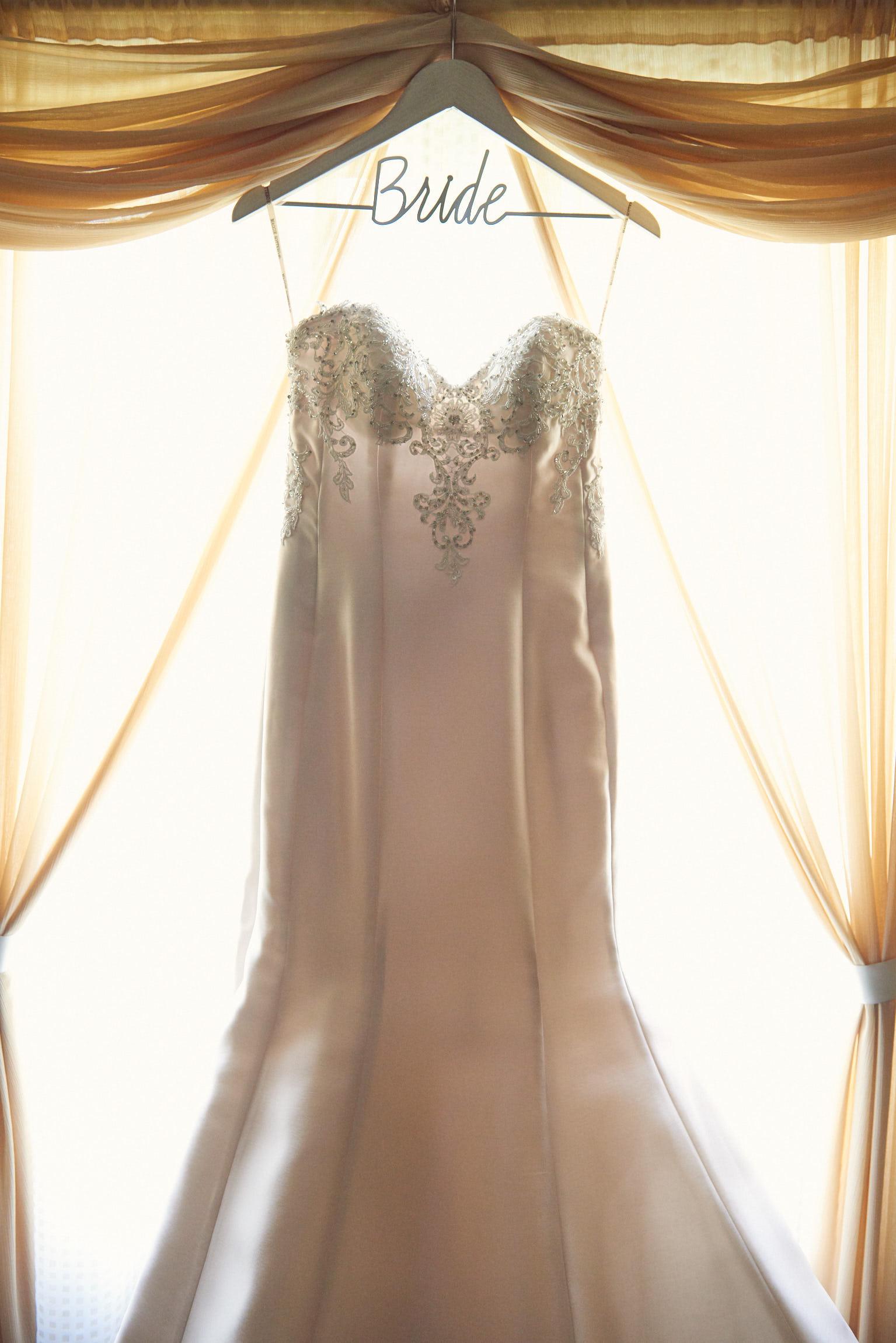 Brides dress hanging on bride hanger