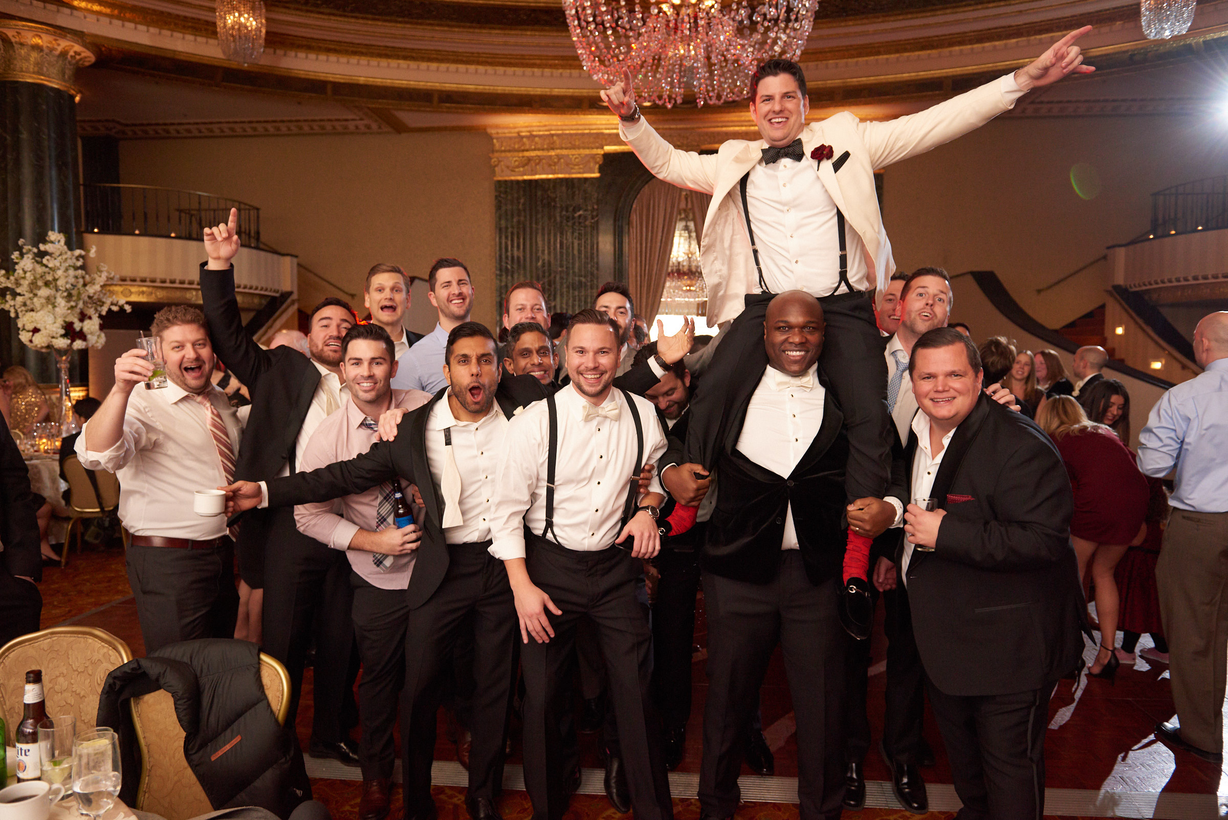 Groom lifted up in the air at reception
